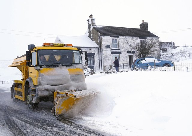 A snow plough making its way along a snow covered road in the village of Harwood in Teesdale, Durham