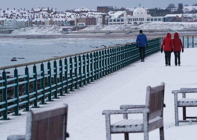People take a walk in snow that has fallen overnight