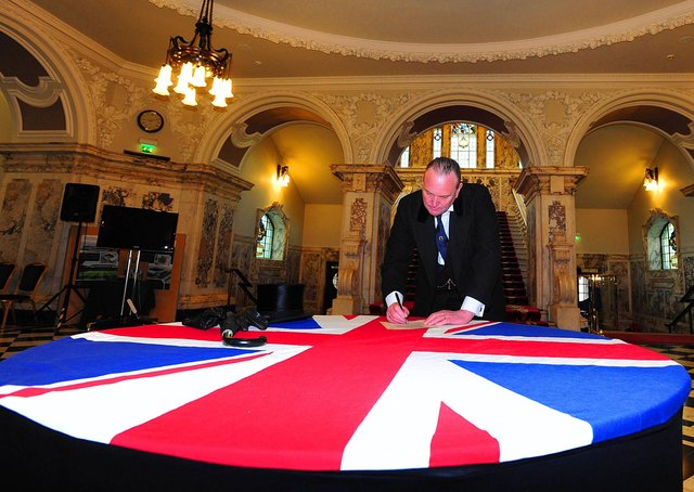 An actor playing Edward Carson re-enacts the signing of the 1912 Ulster Covenant at Belfast City Hall in 2012