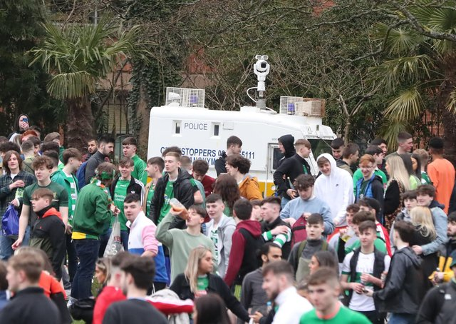 A police vehicle surrounded by people out celebrating in the Botanic Gardens in Belfast, on St Patrick's Day. Picture date: Wednesday March 17, 2021.