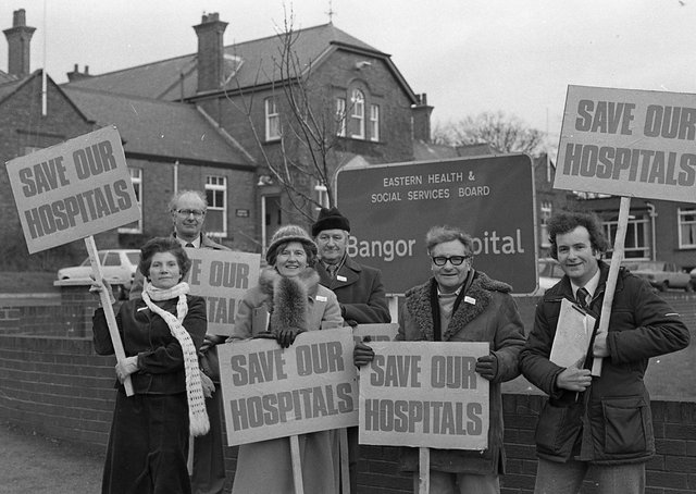 """Cold, and wet, but not dispirited, 19 members of North Down Borough Council had held at 24 hour street vigil as part of a battle to save Bangor and Crawfordburn hospitals which were both threatened under rationalisation plans in 1982. One options being considered by the Eastern Health Board was the closeure Crawfordsburn Geriatric Hospital, transferring the patients to Bangor, which would be downgraded, and to run down Newtownards Hospital, the board was also considering cutting 80 extra beds in the Ulster Hospital at Dundonald. Brian Wilson, a North Down representative on the board, remained optimistic, he told the News Letter: """"I am becoming more hopeful of saving Bangor Hospital. Members of the board are increasingly aware of the feelings of the people of the borough and the hardship it will cause."""" Picture: News Letter archives"""