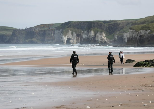 The PSNI – seen here on an almost empty White Rocks beach last Easter – have enforced restrictions vigorously, yet let the Bobby Storey funeral. Photo: Kelvin Boyes/Press Eye.
