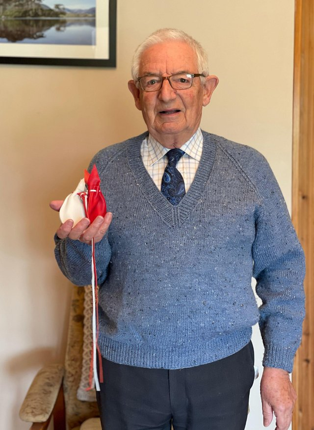 Neville Pogue from County Armagh holding his gift of Maundy money