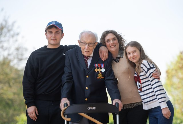 Captain Tom Moore, with (left to right) grandson Benji, daughter Hannah Ingram-Moore and granddaughter Georgia, at his home in Marston Moretaine, Bedfordshire, after he achieved his goal of 100 laps of his garden.