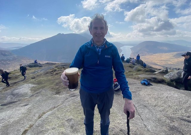 On top of the world: Damien Hamilton stands proudly at the summit of Slieve Doan