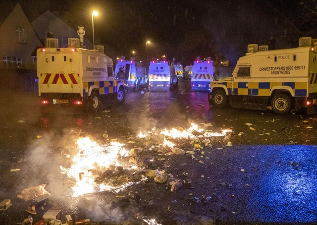 PSNI Tactical Support Group (TSG) officers in attendance at the Loyalist Nelson Drive Estate in the Waterside of Londonderry, during a public order incident which saw a car being set alight and surrounding roads being blocked with fires. Photo: Liam McBurney/PA Wire