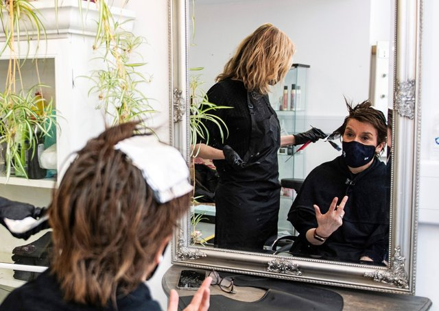 Scotland's First Minister Nicola Sturgeon, wears a face covering, as she has her hair coloured and cut by Julie McGuire at Beehive Hair and Make up hairdressers' salon in Edinburgh, during campaigning for the Scottish Parliamentary election on Easter Monday. Photo: Andy Buchanan/PA Wire