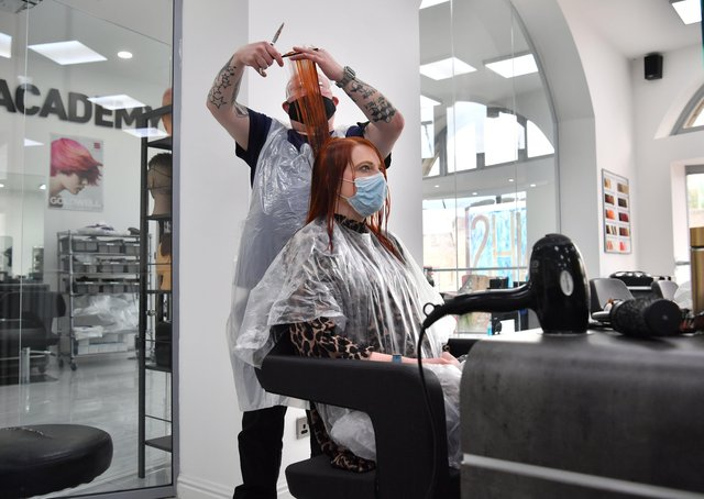 Senior stylist Robert Brooks cuts the hair of Carmen Smith at the Lazarou salon in Cardiff, Wales. Hairdressers and barbers in Wales reopened last month. Picture date: Monday March 15, 2021.