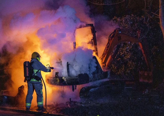 A member of the Northern Ireland Fire and Rescue Service (NIFRS) extinguishes a JCB digger which was set alight close to the Nelson Drive estate in the Waterside, Londonderry.