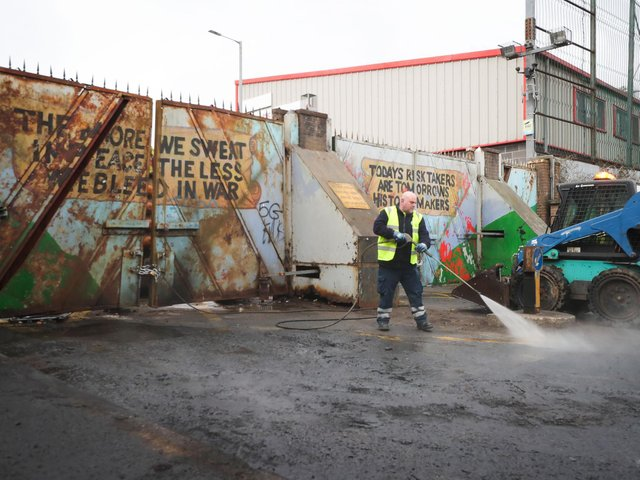 A Belfast City Council workers pictured near the Peace Wall near Lanark Way.