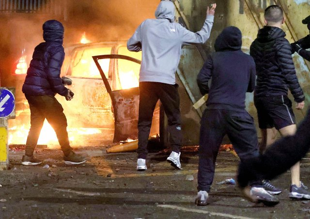 Nationalist youths throw stones at Loyalist throughthe security gate at Lanark Way interface in Belfast during a riot on Wednesday night. Loyalists had blocked traffic during a protest which then erupted into a riot.PICTURE BY STEPHEN DAVISON
