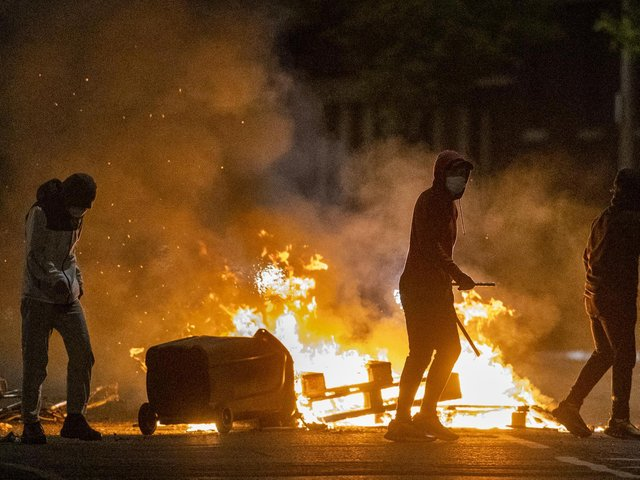 People stand next to a fire in a street in Belfast during further unrest. (Photo: PA)