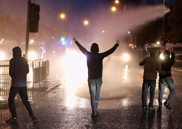 The PSNI use a water cannon on youths on the Springfield road, during further unrest in Belfast on Thursday. Photo: Liam McBurney/PA Wire