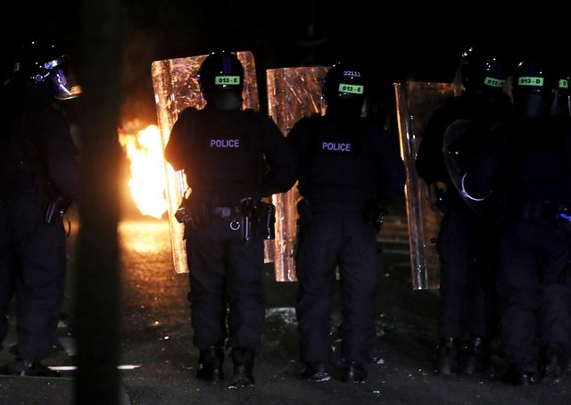 PSNI officers look on after a Loyalist rioter threw a petrol bomb in the Tigers Bay Area of North Belfast during further unrest in Northern Ireland. Picture date: Friday April 9, 2021
