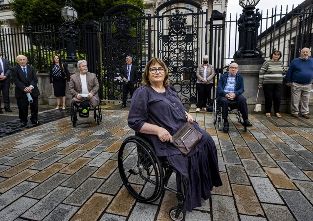 Belfast bomb victim Jennifer McNern (centre) poses outside Belfast's High Court with with legal team and members of the Wave Trauma Centre in support of the challenge to delays over the Troubles pension.