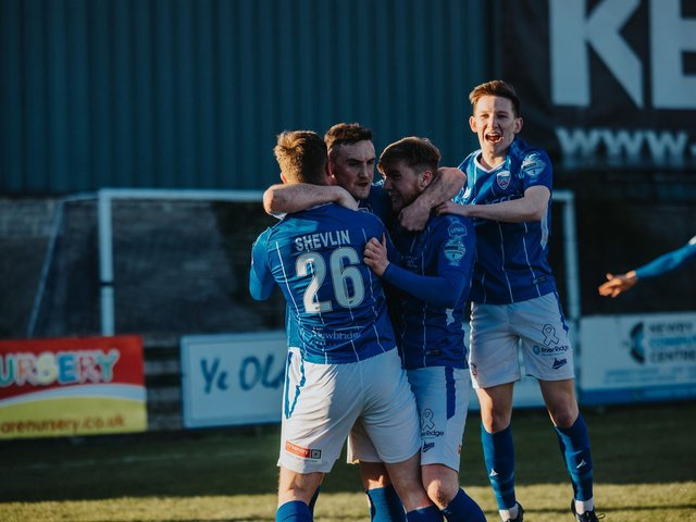 Stephen O'Donnell is mobbed by his team-mates after his winner against Warrenpoint Town. PICTURE: David Cavan