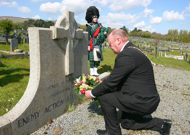 Lord Mayor of Belfast Alderman Frank McCoubrey laying a wreath at Milltown Cemetery while piper Matthew Wilson plays Abide With Me