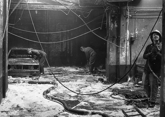 News Letter staff clearing up the garage where the accidental fire was believed to have started in April 1980. Picture: News Letter archives