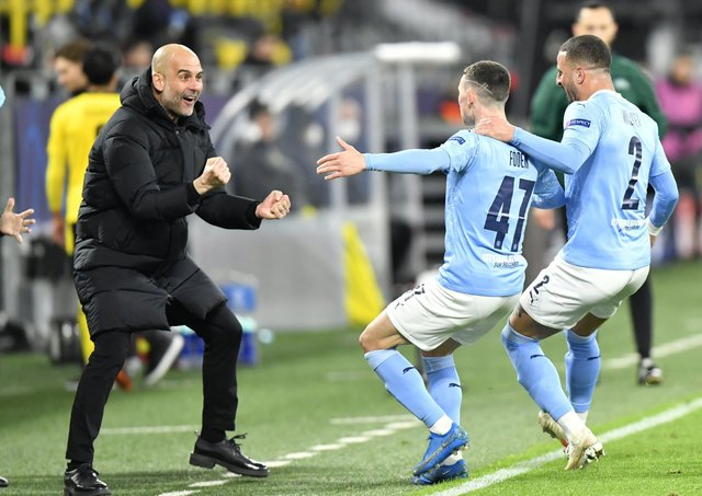 Manchester City manager Pep Guardiola celebrates with goal scorer Phil Foden and Kyle Walker (right) after their second goal during the UEFA Champions League, quarter final, second leg match at Signal Iduna Park in Dortmund, Germany.