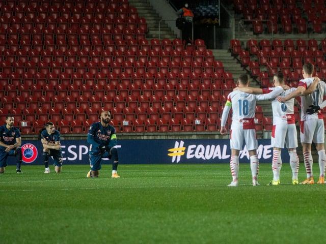 Arsenal's Alexandre Lacazette (C) and his team-mates take a knee prior to the UEFA Europa League quarter-final second leg football match against Slavia Prague