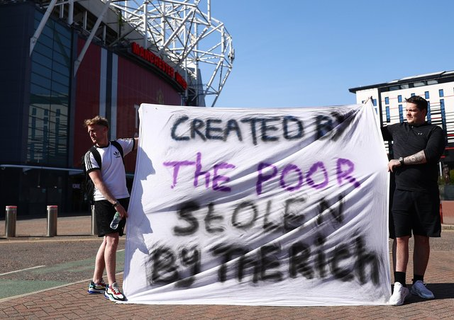 Football fans opposing the European Super League outside Old Trafford in Manchester on Monday.