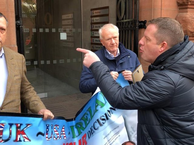 Gareth McCord (right), the brother of a paramilitary murder victim, interrupts LCC chairman David Campbell (left) and former Ulster Unionist MLA and UKIP NI leader David McNarry (centre) during a small loyalist protest against Brexit's Northern Ireland Protocol outside the Irish Secretariat offices in Belfast.