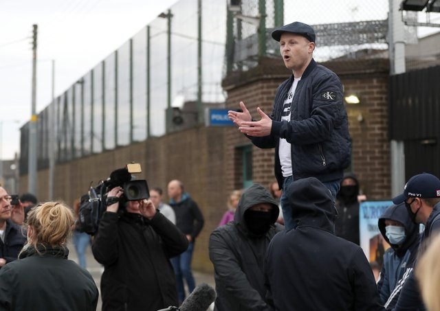 Jamie Bryson speaks to the gathered crowd outside Newtownards PSNI Station during a recent protest.