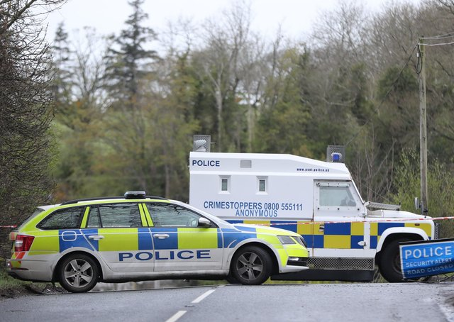 PSNI vehicles block a road during a security operation which has been ongoing since Monday on the Ballyquin Road after a viable explosive device was found close to the home, in a rural area close to Dungiven, of a member of the Police Service of Northern Ireland in Co Londonderry. Pic: Niall Carson/PA Wire