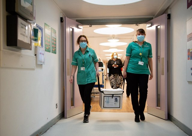 Pharmacists transport a cooler containing the Moderna vaccine, at the West Wales General Hospital in Carmarthen, the third vaccine to be approved for use in the UK, to be given to patients in Wales. Picture date: Wednesday April 7, 2021.
