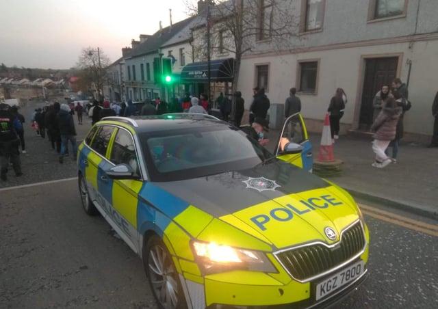 Protestors in Markethill last night walk past a PSNI car