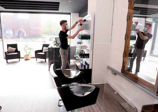 Press Eye - Belfast - Northern Ireland - 22nd April 2021  Business across Northern Ireland, including hairdressers and tattoo studios, prepare for reopening tomorrow as COVID-19 lockdown restrictions across the country are eased.    Hairdresser Adam Scott  helps prepare the Andrew Watson salon on the Lisburn Road, south Belfast, for opening.   Picture by Jonathan Porter/PressEye