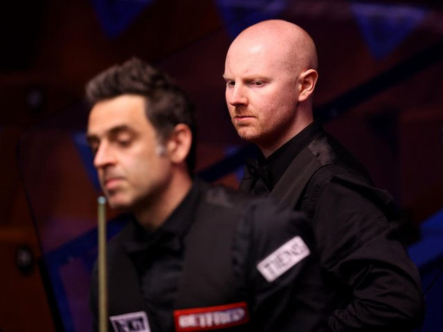 Anthony McGill looks on behind Ronnie O'Sullivan during their match in the Betfred World Snooker Championships