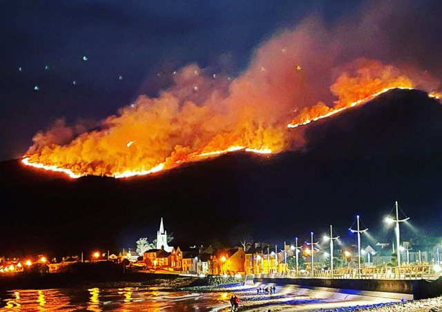 Photo taken with permission from the Twitter feed of @DeeJayDready showing a huge gorse fire spreading across the Mourne Mountains in Co Down, as seen from Newcastle, Co Down. The fire in the Slieve Donard area has been ongoing since the early hours of Friday morning, with up to 60 firefighters and 12 appliances battling the blaze. Issue date: Saturday April 24, 2021.