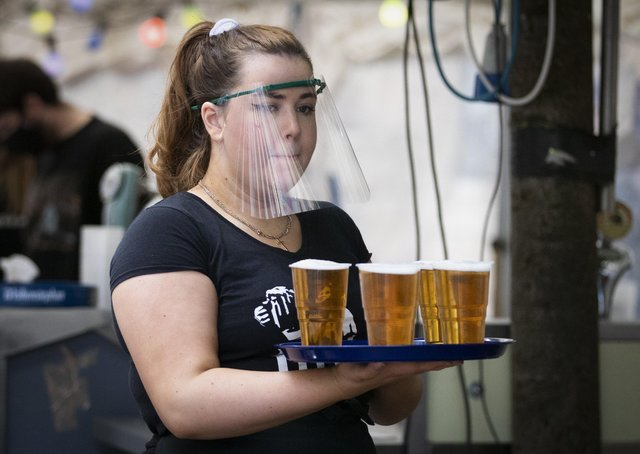 A member of staff serves drinks in the beer garden at the Bier Halle, Glasgow, where outdoor areas have already reopened to the public