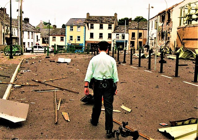 A policeman walks through the aftermath of an INLA car bomb attack against the village of Newtownhamilton, Co Armagh, on June 24, 1998; the explosives detonated just as RUC officers were clearing people away from the area, wounding at least three people and wrecking the village's centre