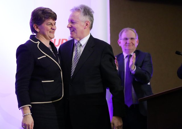 December 17, 2015: New leader of the DUP Arlene Foster pictured alongside Peter Robinson, just after her takeover was announced; applauding in the background is longtime DUP chairman Lord Morrow