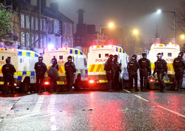 A line of police at disturbances in west Belfast last month; the poll asked if re-unification would strain peace further