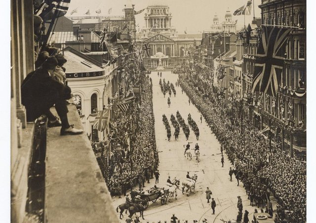View from top floor window of building on corner of Castle Place and Royal Avenue showing crowds watching the Royal Procession approaching the City Hall for the state opening of the first Northern Ireland Parliament 22 June 1921, with people sitting on window ledge. Catalogue number:BELUM.Y22657. Robert John Welch, (1859-1936), © National Museums NI, Collection Ulster Museum