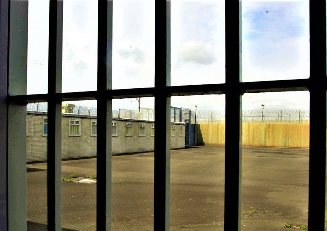 Looking through a cell's bars at an exercise yard at The Maze prison