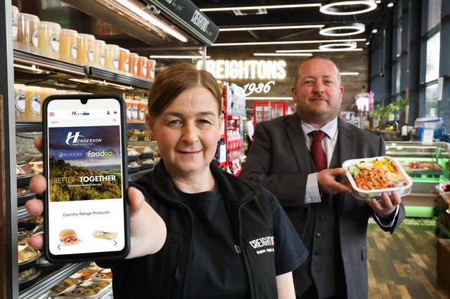 Elaine Williams, Development Manager with Creightons Group helps Chris Palmer, E-Commerce lead with Hendersons celebrate the company's Akeneo leadership award