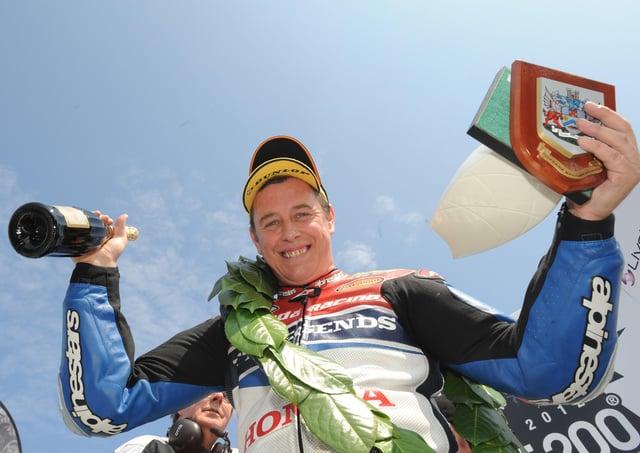 Honda TT Legends rider John McGuinness celebrates winning the opening Superbike race at the 2012 North West 200.