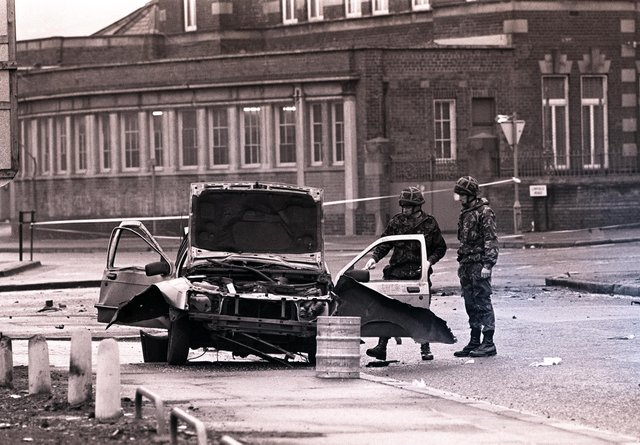 Belfast, 1991: Two soldiers survey a taxi, blown up with the driver and his lady passenger inside