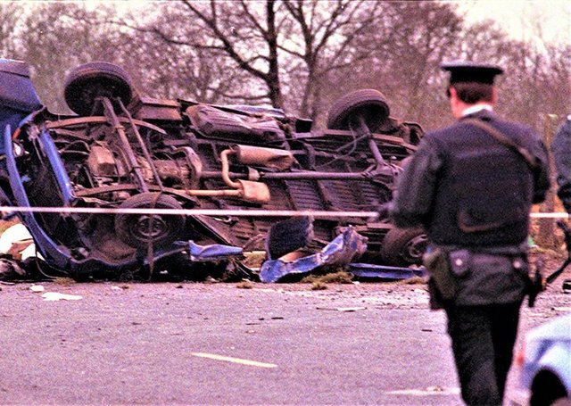 A policeman stands guard by a destroyed vehicle carrying 14 Protestant workmen in the Teebane area of Co Tyrone, 1992. The IRA attack killed eight