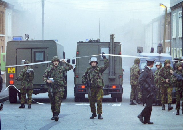12/01/1994 Soldiers attempt to clear the area in Spamount Street, Belfast, as a booby trap bomb explodes. A woman soldier was earlier shot in the neck and back by a sniper in the area