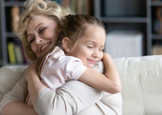 A happy grandmother hugs her granddaughter
