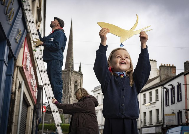 Five year old Thea Johnston, Enniskillen Integrated Primary helps artist Simon Carman and Helen Sharp as they begin the installation150 little swallows in gold leaf in and around Enniskillen centre. Picture by Brian Morrison.