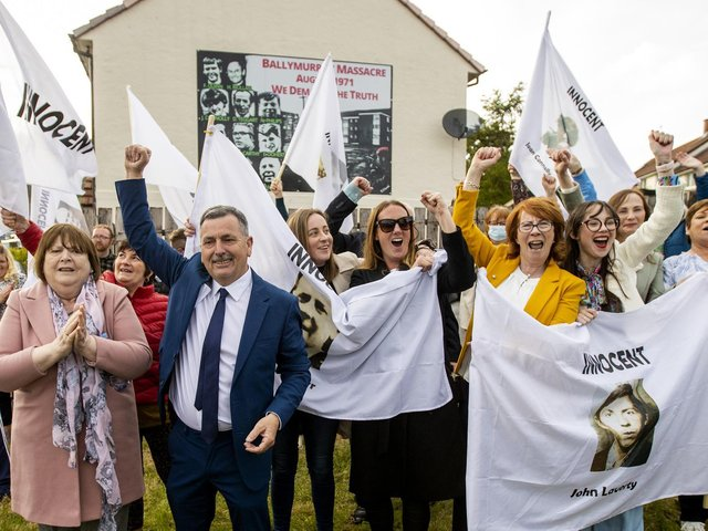 """The families of the victims and supporters waving white flags with the words """"innocent"""" on them, in Ballymurphy, just hours after a coroner ruled that the 10 people killed in the west Belfast shootings involving British soldiers in Ballymurphy in August 1971 were entirely innocent."""