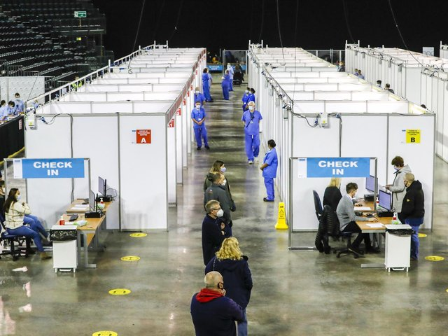 People wait in line to receive their Covid-19 vaccine in the SSE Arena, Belfast.