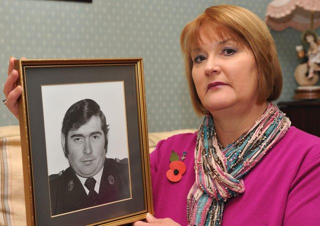 Phyllis Carrothers holds a photograph of her late husband Dougie