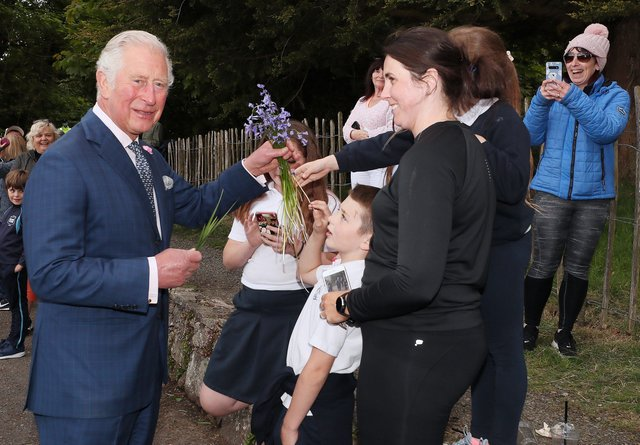 Charles is presented with a bunch of bluebells by a south Armagh family during his visit to Slieve Gullion Forest Park.
